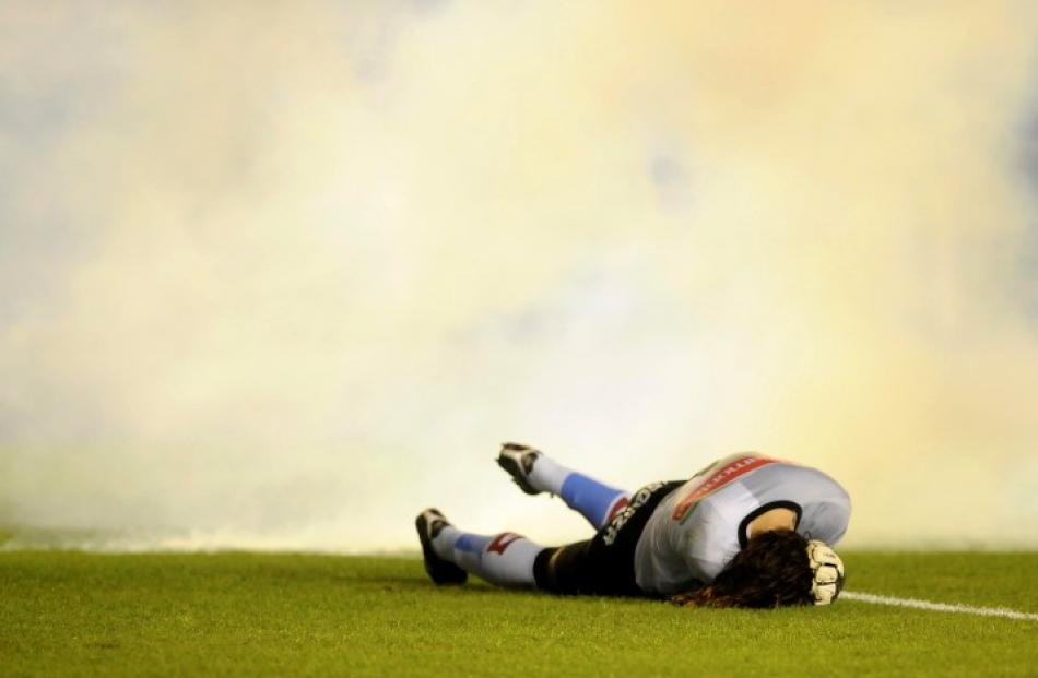 Goalkeeper Juan Carlos Olave from Argentine football club Belgrano lies on the pitch after being...