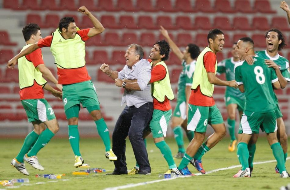 Iraq's head coach Zico (C) of Brazil celebrates with his players during their 2014 World Cup...