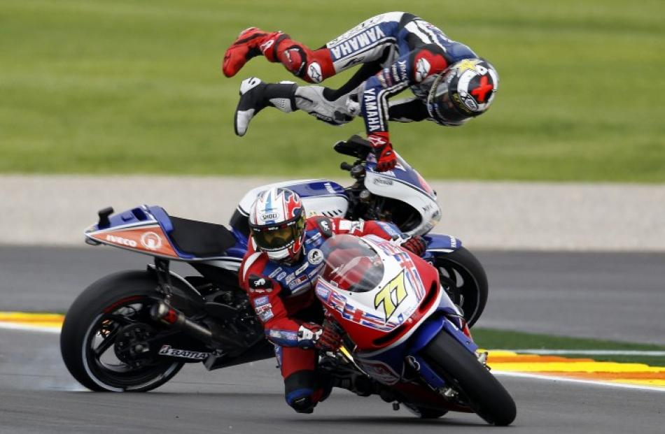 Yamaha rider Jorge Lorenzo (back) comes off behind James Ellison of Britain during the Valencia...