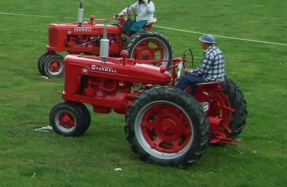 "A pair of vintage Farmalls take part in a ""tractor dance""."