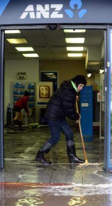 Sandra Wilson sweeps water out of the ANZ bank.