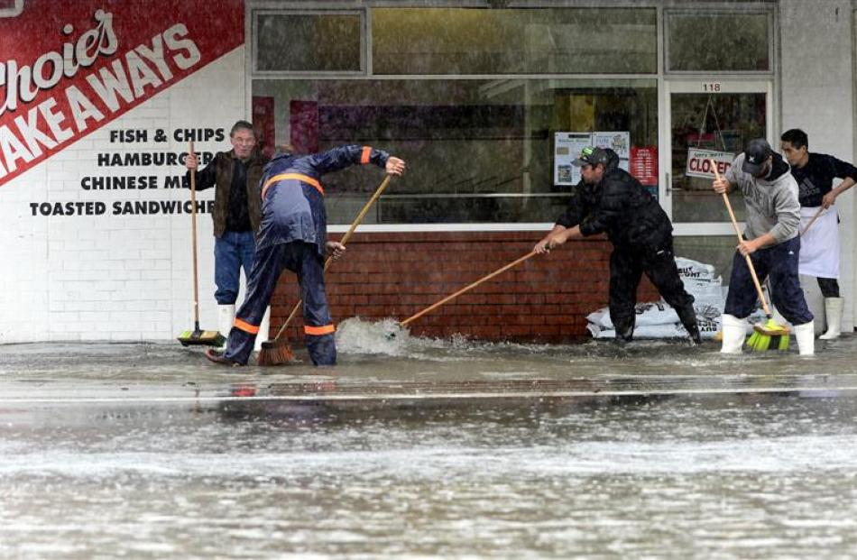 Trying to keep the water away from Mosgiel businesses are (from left) Larry Greenall, Jeff Wilson...