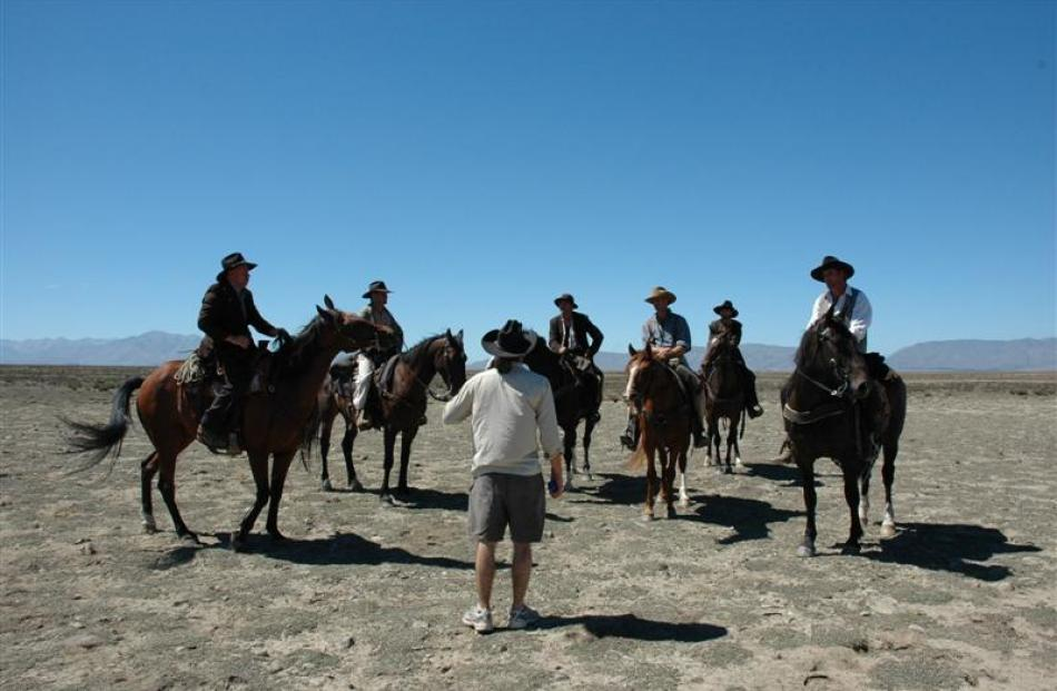 Director Mike Wallis talks to posse riding doubles on location  during the production of Good for...
