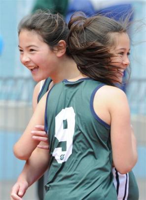 Columba College relay runner Maia Joseph (No 9) embraces team-mate Nikita Horne (both 10)