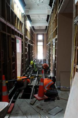 Contractors carry out strengthening work in a hallway.