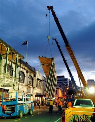 Cranes combine to remove part of the Harvest Court Mall facade on Tuesday night.
