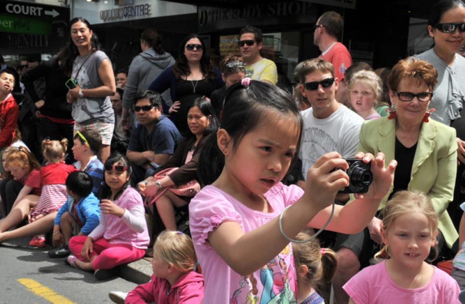 Phoebe Cooper (6) takes photos of the parade.