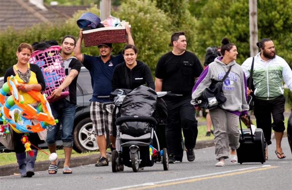 People take their belongings with them as they are evacuated from their damaged homes in...