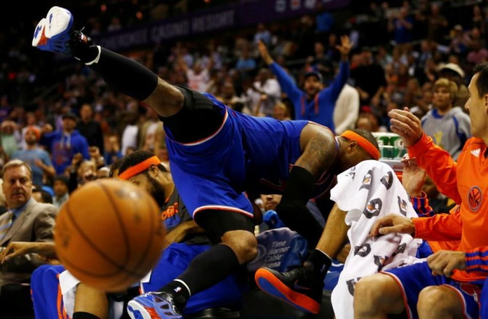 New York Knicks small forward Carmelo Anthony dives into his team's bench as he chases a loose...