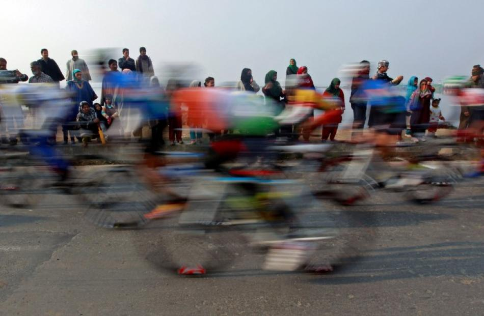People watch a peloton of riders cycle past them during the second leg of the Tour de India...