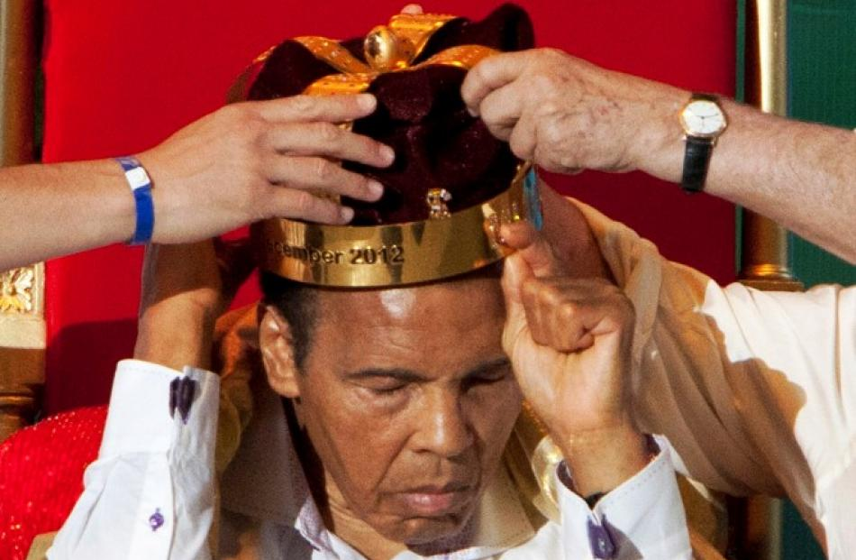 The crown of 'King of Boxing' is placed on former American boxer Muhammad Ali during the 50th...