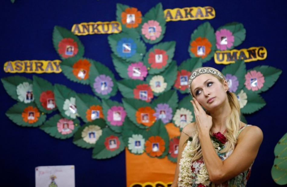 Socialite Paris Hilton listens to a speaker during her visit to an orphanage in Mumbai, India....