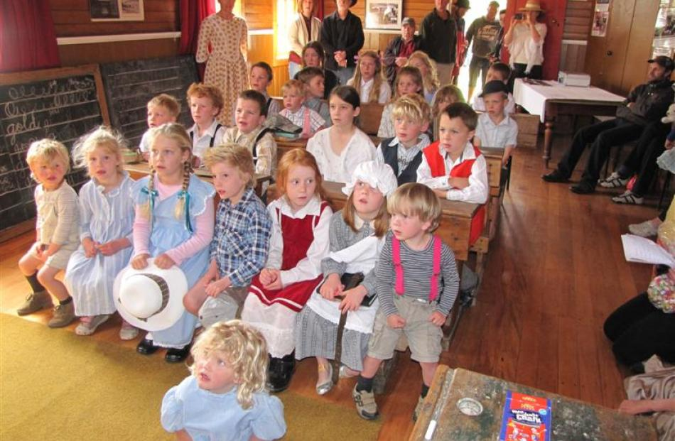 Children listen attentively (left) during a period class re-enactment in the Cardrona Hall.