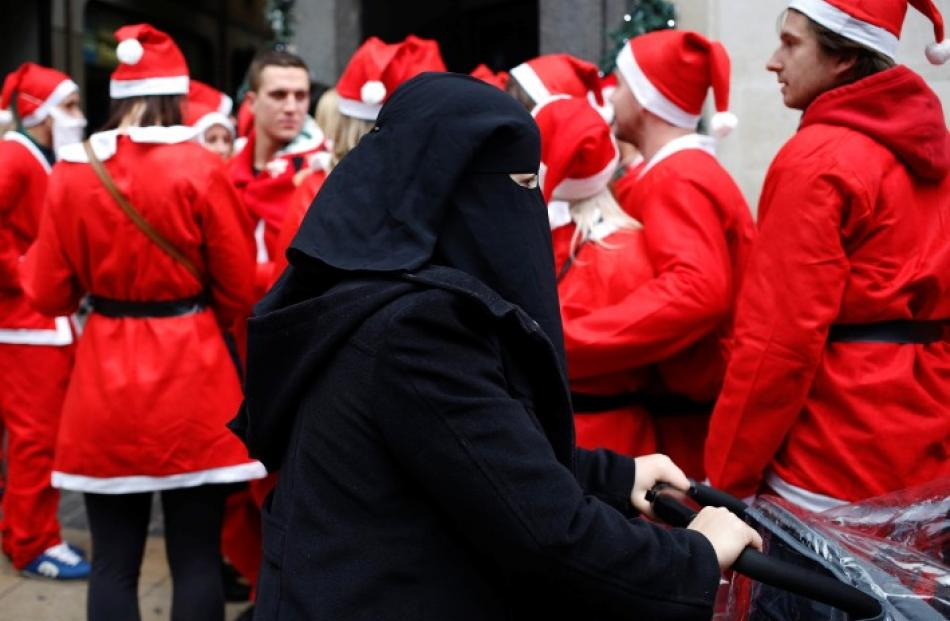 A woman wearing a niqab passes a group of people dressed as Father Christmas on a Santa-themed...