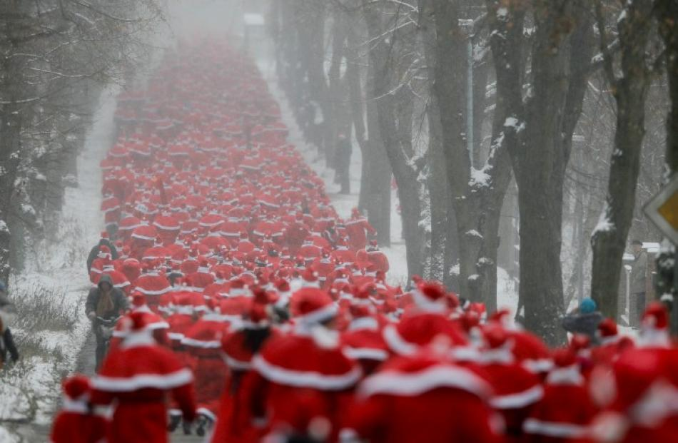 Runners dressed as Father Christmas take part in the so-called 'Nikolaus Run' in the East German...