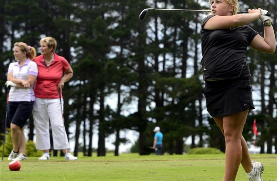 Otago No 1 Laura Hoskin hits off the tee while team-mates Jo Hicks-Beach (left) and Liz McRae...