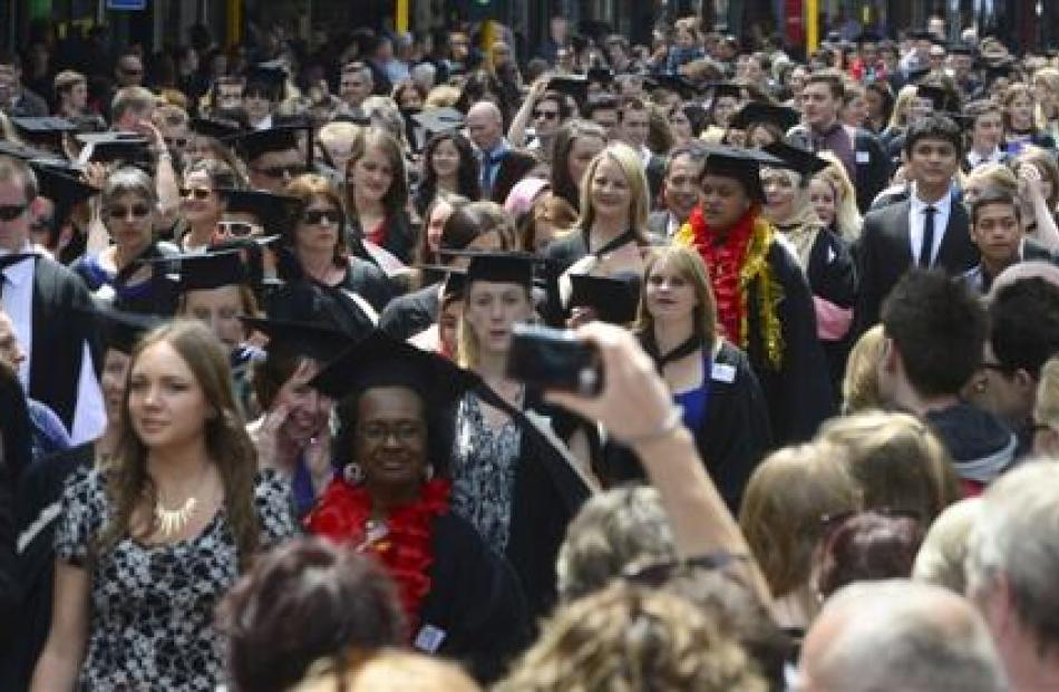 Relatives and other well-wishers watch graduands head along George St, Dunedin, before their...