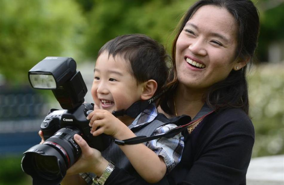Tammy Leong checks pre-graduation photographs at the University of Otago yesterday, with a little...