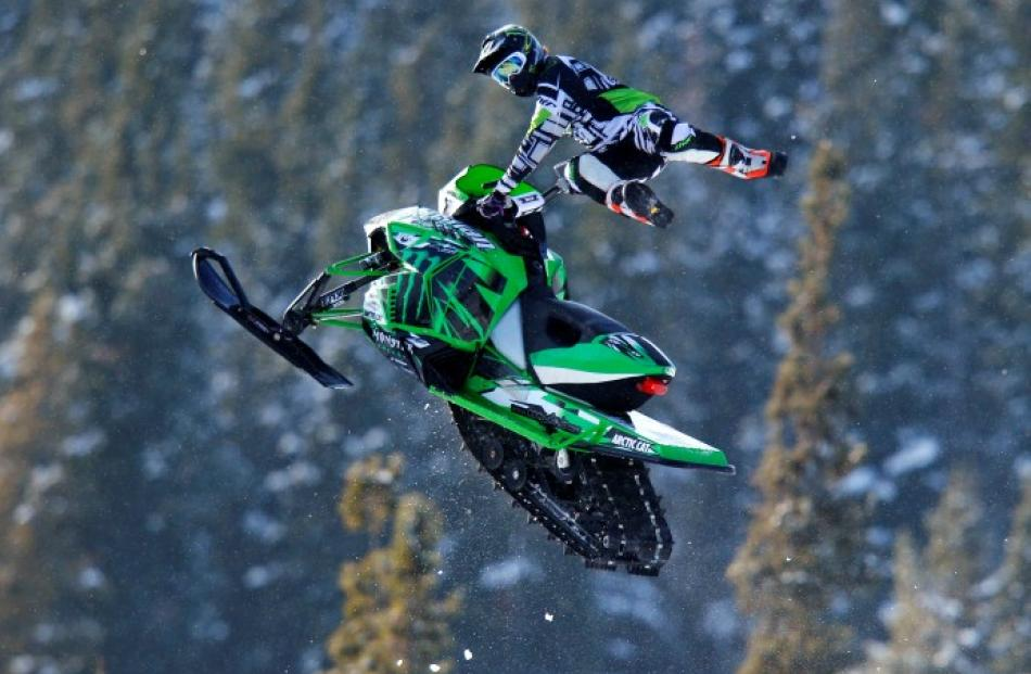A snowmobiler flies through the air during the Monster Energy Snowmobile Freestyle tour at the...