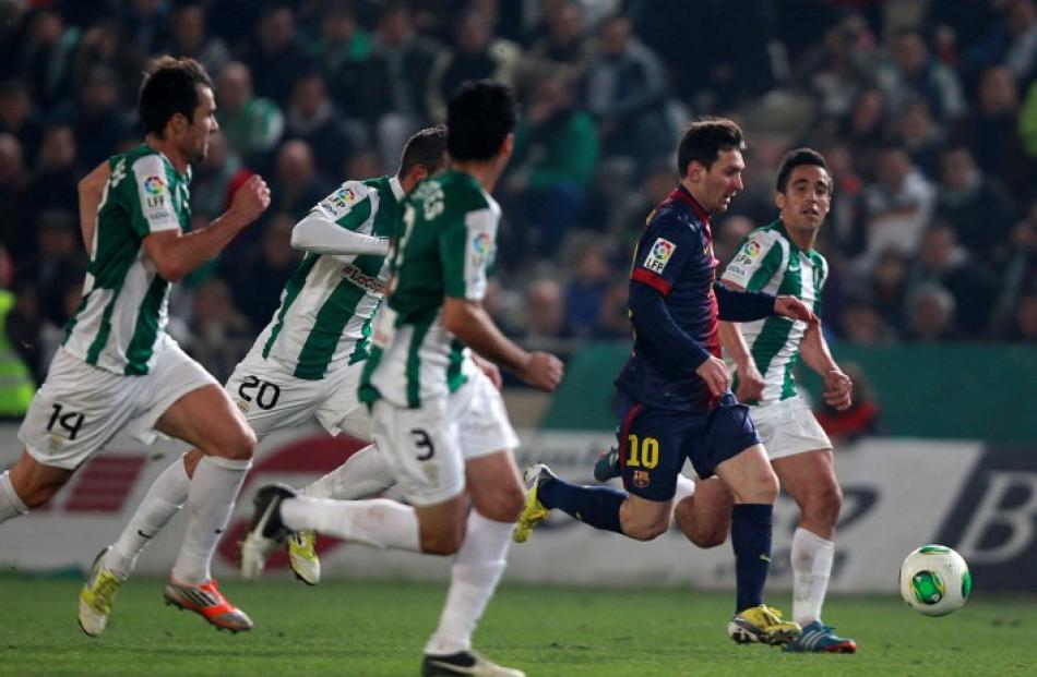 Barcelona's Lionel Messi (2nd R) is chased by Cordoba's players during their Spanish King's Cup...