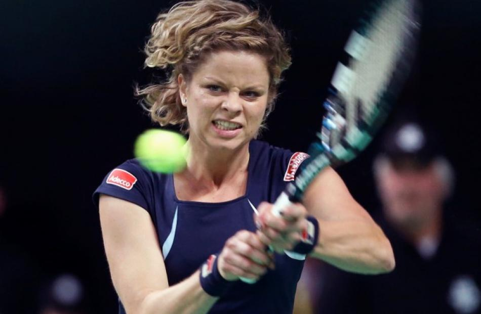 Belgium's Kim Clijsters hits a return to Venus Williams of the US during an exhibition tennis...