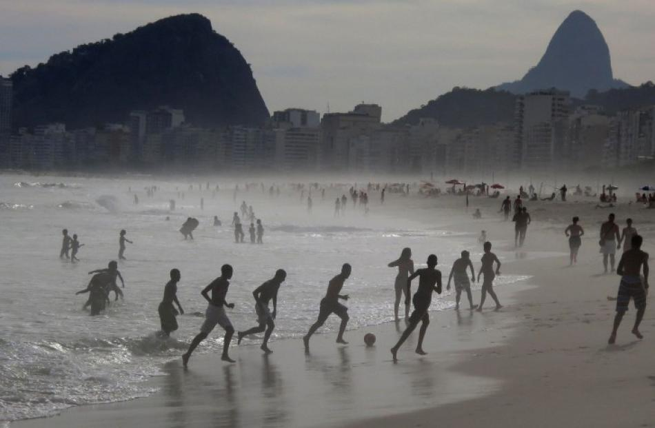 Boys play football at the edge of the surf at Copacabana Beach in Rio de Janeiro, Brazil. REUTERS...