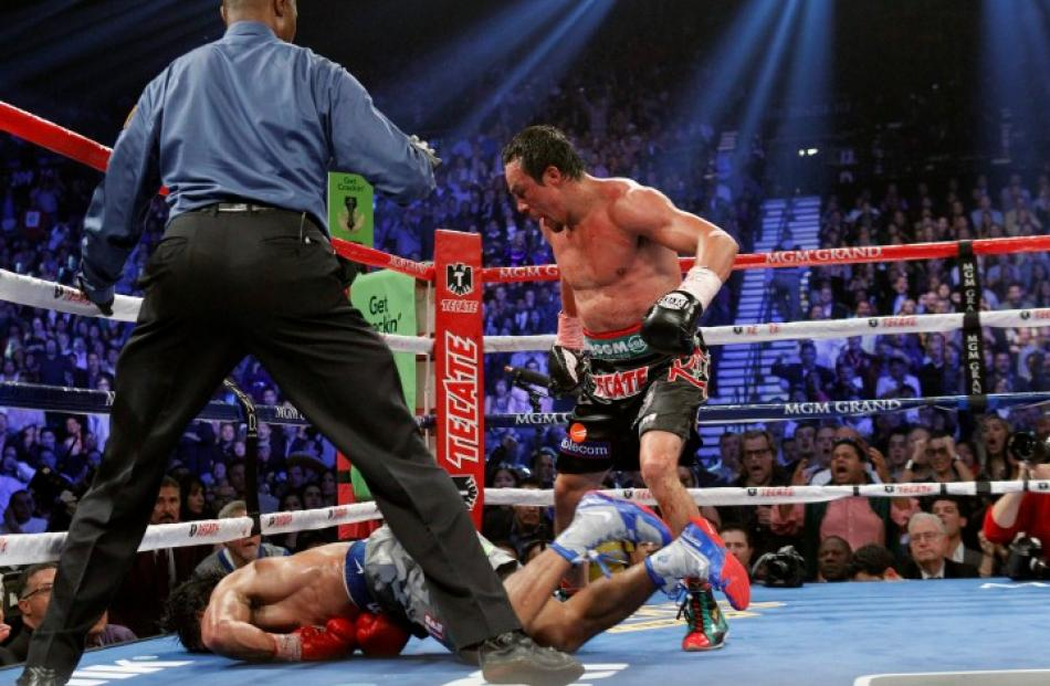 Juan Manuel Marquez (R) of Mexico steps away after knocking out Manny Pacquiao of the Philippines...