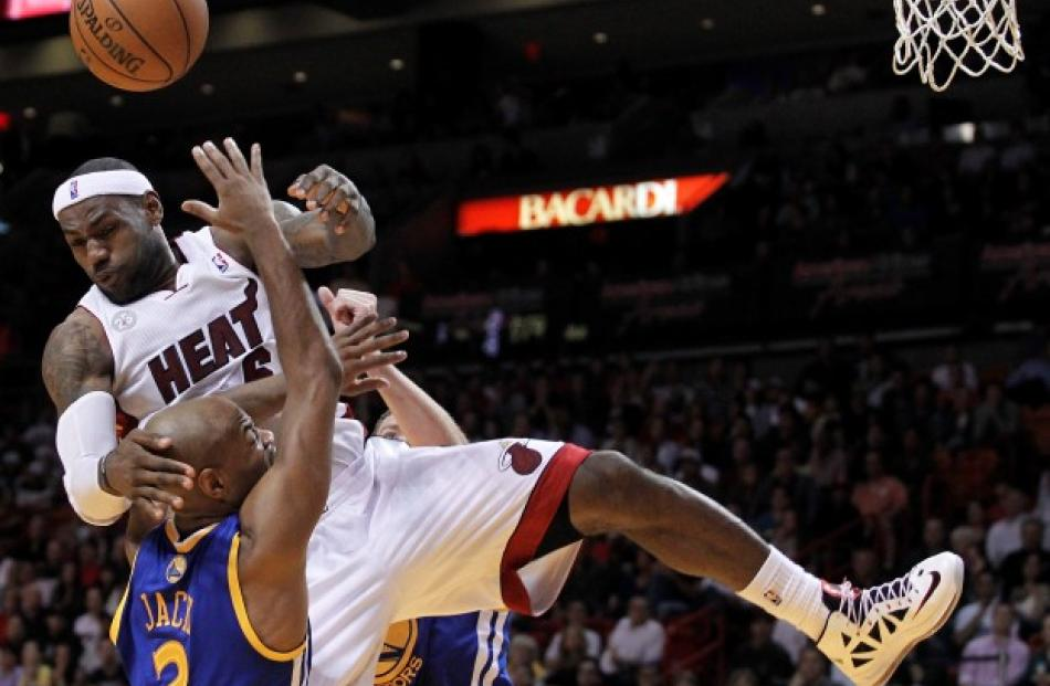 Miami Heat's LeBron James is sandwiched between Golden State Warriors Jarrett Jack and David Lee ...