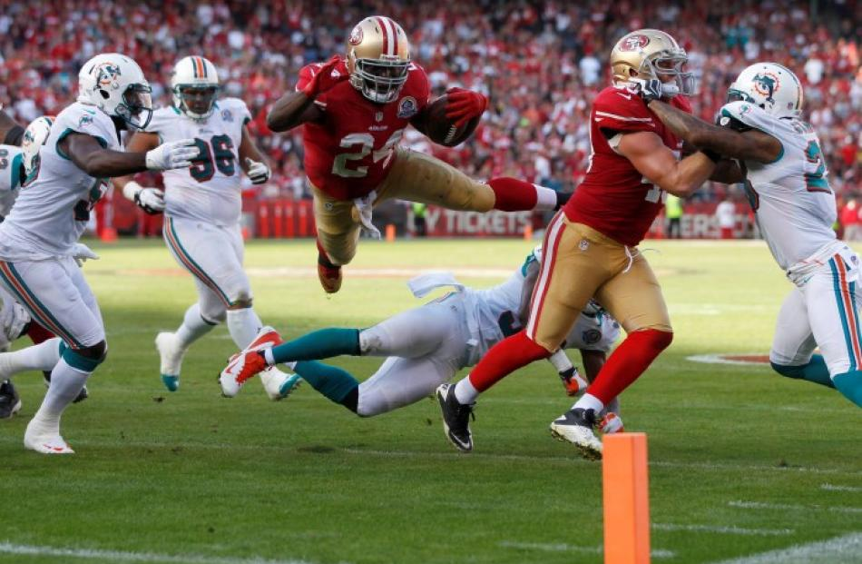 San Francisco 49ers running back Anthony Dixon (C) leaps over Miami Dolphins defenders to take...