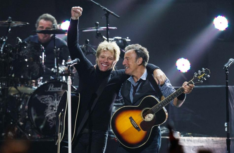 Singers Bon Jovi (L) and Bruce Springsteen perform during the '12-12-12' concert in New York....