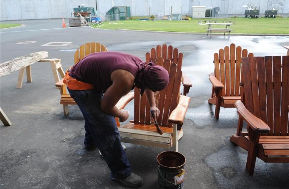 A prisoner stains outdoor chairs.