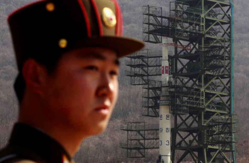 A soldier stands guard in front of the Unha-3 (Milky Way 3) rocket sitting on a launch pad at the...