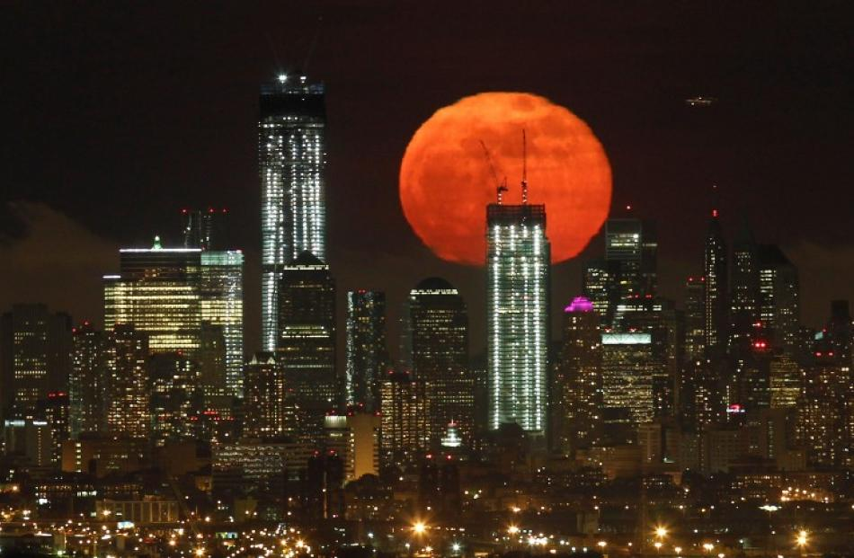 A full moon rises over the skyline of Lower Manhattan and One World Trade Center (L) in New York...