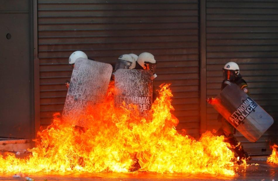 A group of riot policemen is engulfed in flames after protesters threw petrol bombs in Athens'...