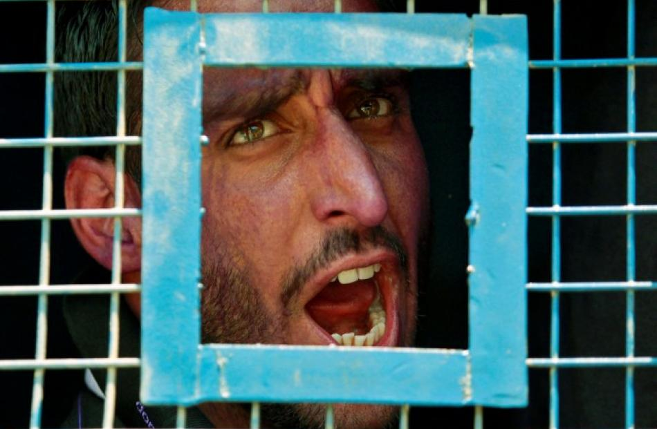 A Kashmiri government teacher shouts anti-government slogans from inside a police van after he...