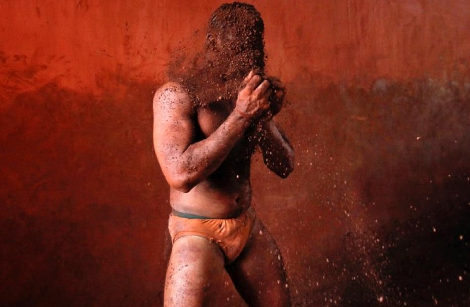 A wrestler rubs his hands with mud to prevent slipping due to sweat during a traditional mud...