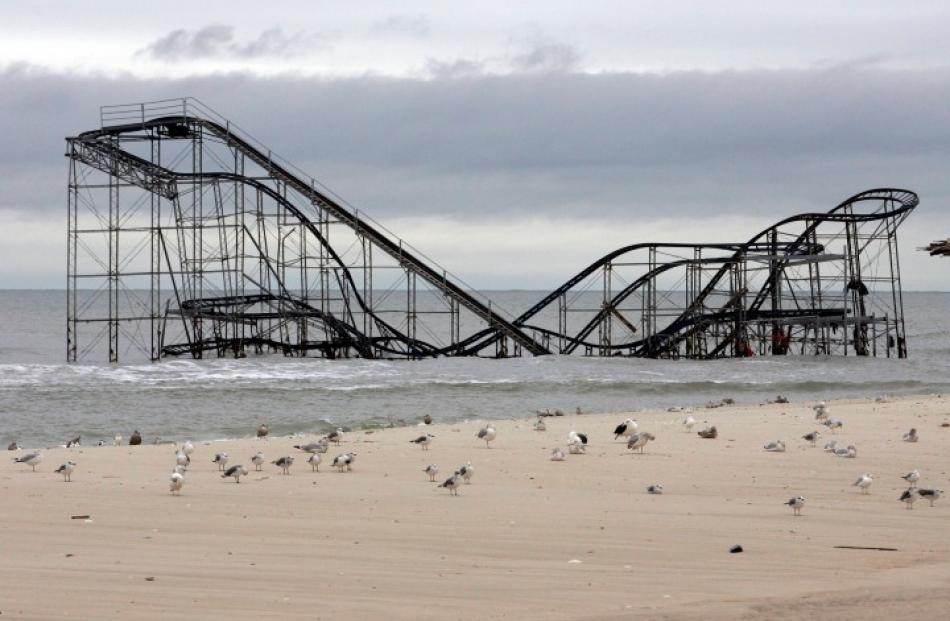 An amusement park roller coaster lies partially submerged in Seaside Heights, New Jersey after...