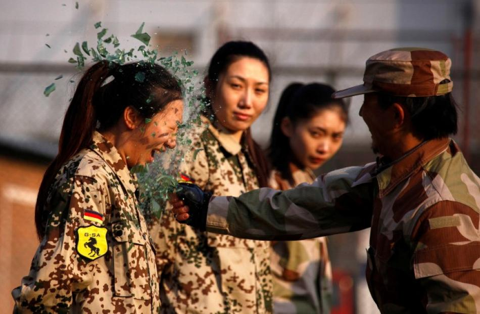 An instructor from the Tianjiao Special Guard/Security Consultant Ltd. Co smashes a bottle over a...