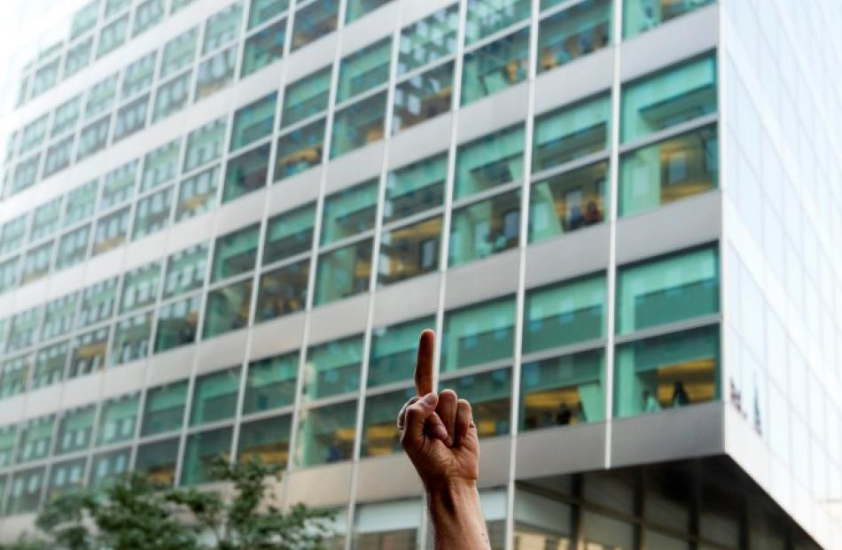 An Occupy Wall Street demonstrator gestures at Goldman Sachs employees watching demonstrations...
