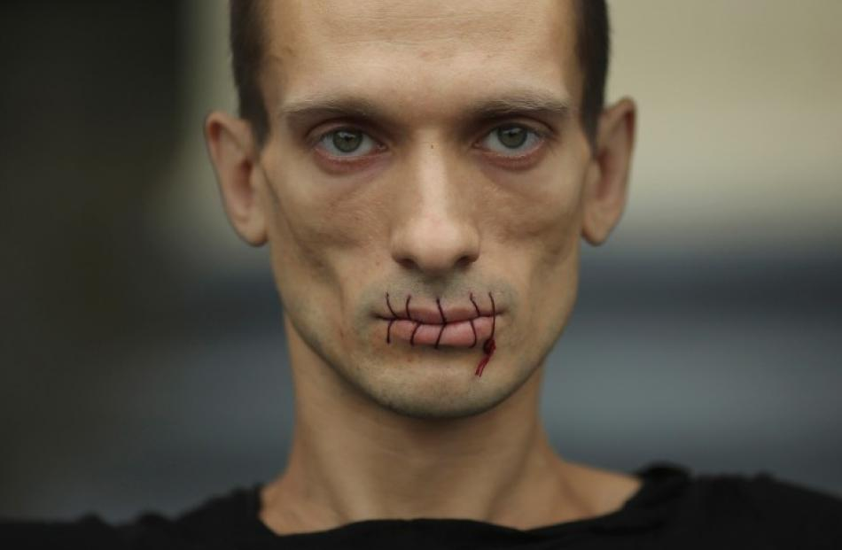 Artist Pyotr Pavlensky, with his mouth sewn up, takes part in a protest in support of Russian...