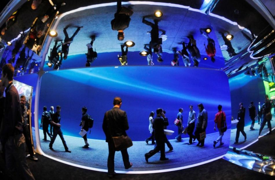 Attendees pass between display areas during the Electronic Entertainment Expo (E3), in Los...