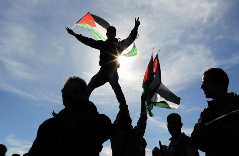 Palestinians wave flags during a rally marking the UN General Assembly's upgrading of the...