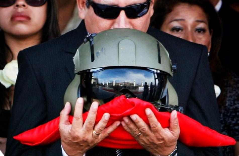 The father of Captain Nancy Flores kisses her pilot helmet during her funeral in Lima, Peru in...