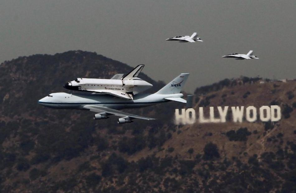 The Space Shuttle Endeavour is escorted by two F18 jets as it passes the Hollywood sign on the...