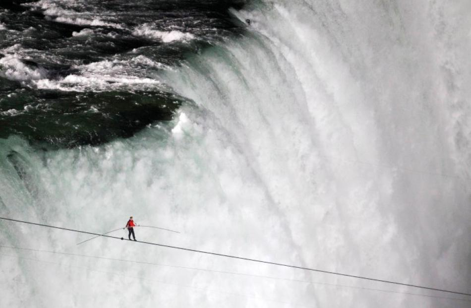 Tightrope walker Nik Wallenda walks the high wire from the US side to the Canadian side over the...
