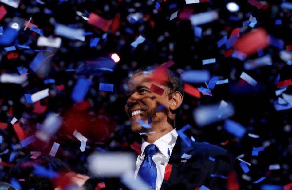US President Barack Obama celebrates on stage as confetti falls after his victory speech during...