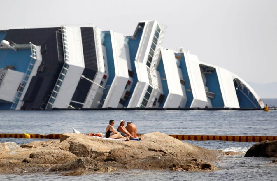 Vacationers bask in front of the wreckage of capsized cruise liner Costa Concordia near the...