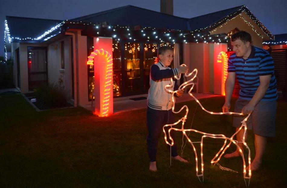 Mosgiel resident Jason Merrett and his son, Blake, install Christmas decorations outside their...