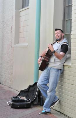 Kristopher Bate sings and plays his guitar in Albion Way on Saturday afternoon.