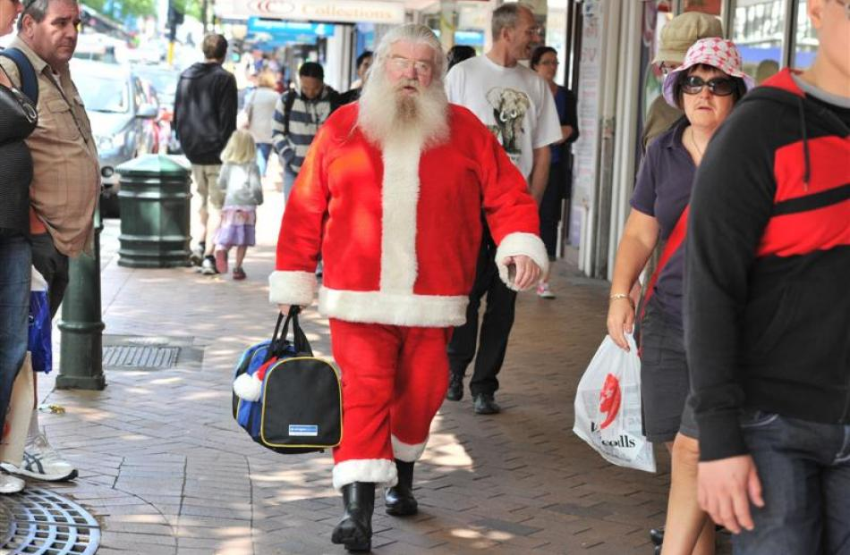 Santa makes his way past  shoppers on his way to Santa's Grotto at Dunedin's Golden Centre Mall...